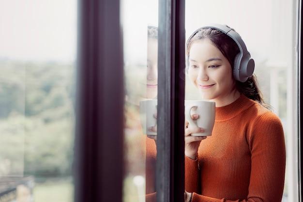 音楽を聴くと窓のそばに立っている間カップを保持しているオレンジ色のセーターの若い女性。