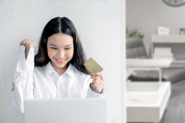 クレジットカードを保持しているラップトップコンピューターを使用して若い女性。オンラインショッピング。