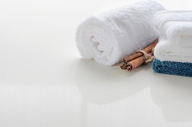 コピースペースを持つ白いテーブルに白いタオルのロールアップ。製品表示モンタージュのコピースペース。