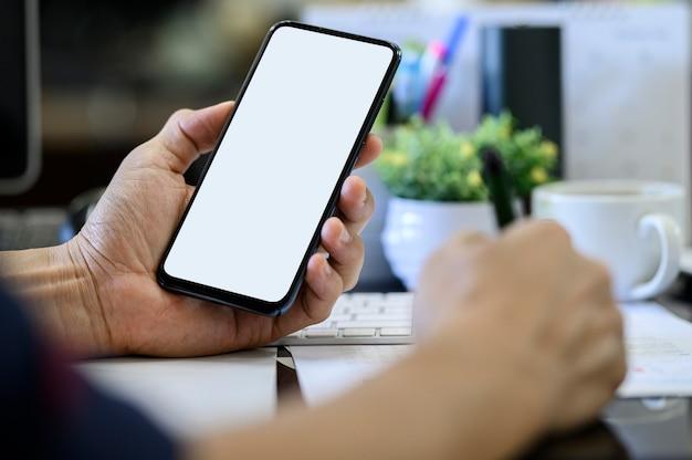 オフィスの机で働いている間空白の白い画面を持つスマートフォンを持っているクローズアップ男の手。