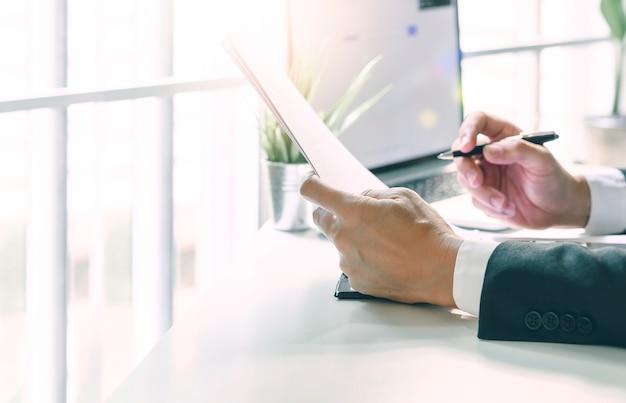 近代的なオフィスのオフィスの机に座って書類とペンを持っているクローズアップ実業家の手。