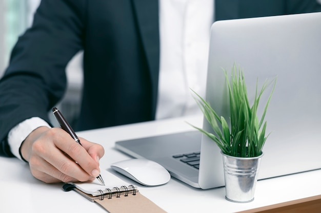 クローズアップは、近代的なオフィスでノートパソコンで作業しながらノートに書くペンを使用して実業家を撮影しました。