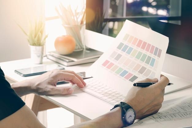スタジオでカラーチャートとコンピューターで作業するクローズアップのプロのデザイナー。