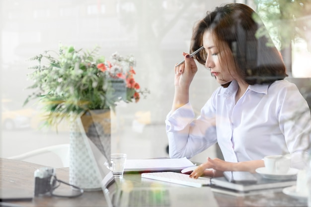 Портрет молодой ручки удерживания коммерсантки и думать о новом проекте пока сидящ в современном офисе, смотря через стекло окна.