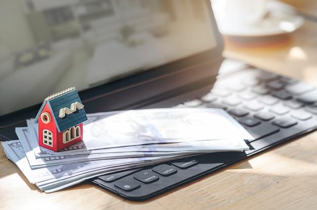 Деревянная модель дома и банкнота на клавиатуре планшета.