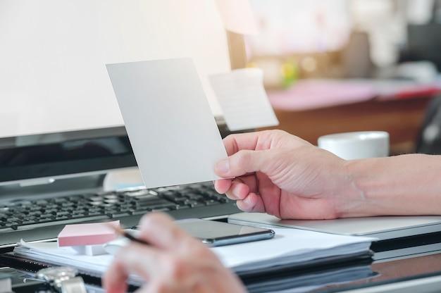 クローズアップ男の手が空白のカードを押しながらオフィスの机に座って、デスクトップコンピューターでの作業
