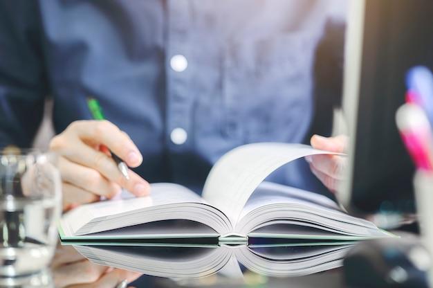 Человек крупного плана раскрывая и читая книгу пока сидящ на таблице в офисе.