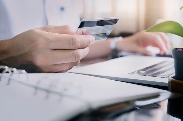Рука человека крупного плана держа кредитную карточку пока сидящ на столе офиса в современном офисе.