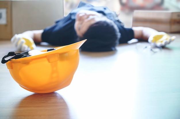 Желтый шлем раненого лежа работника на работе.
