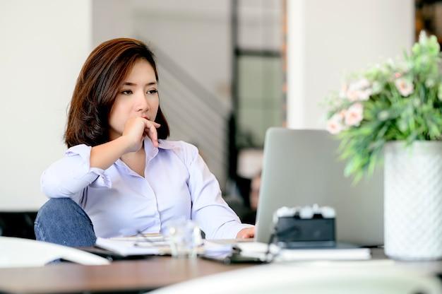 Скучно молодая бизнесвумен, сидя на рабочий стол во время работы с ноутбуком.