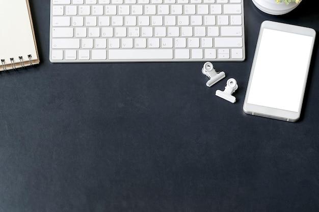 青い革背景に事務用品とトップビューオフィスデスク。