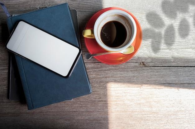 モックアップスマートフォン白い空白の画面と木製のトップテーブルにコーヒーカップ。