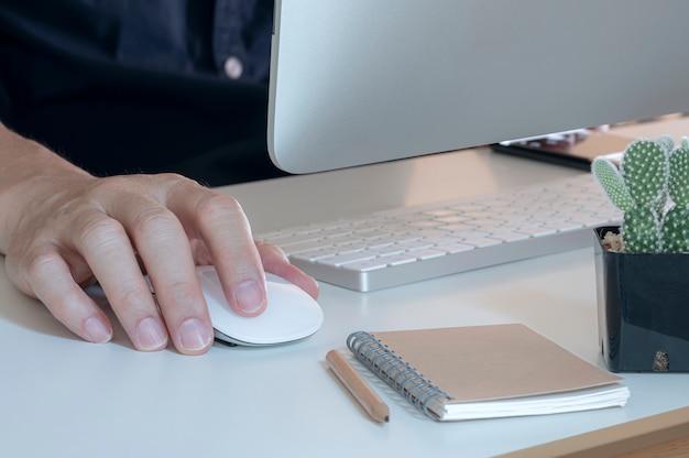 コンピューターのマウスを扱う人間の手
