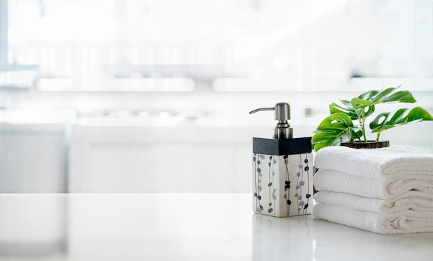 セラミックシャンプー、石鹸のボトル、キッチンルームのカウンターでタオル。白いトップテーブルとコピースペース。