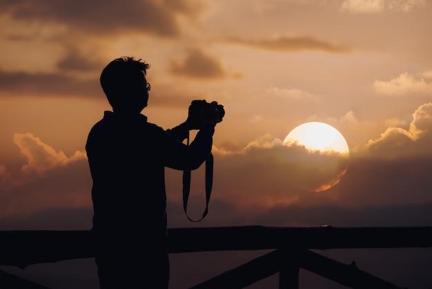 人の写真家のシルエットは、日没の背景で写真を撮る