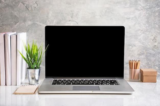 コンクリート壁の白いテーブルにオフィス用品を備えたモックアップラップトップコンピュータラップトップ