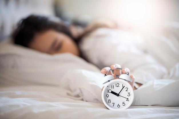 女性は午前中に遅く起きて、目覚まし時計をオフにしようとします。