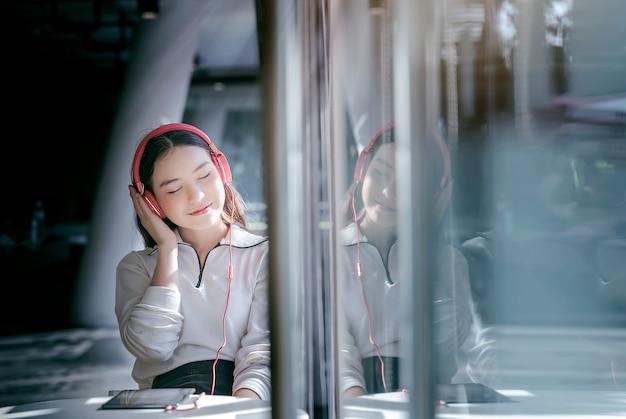 女性は赤いヘッドホンでタブレットの中に座っている間、目を閉じて音楽を聴く