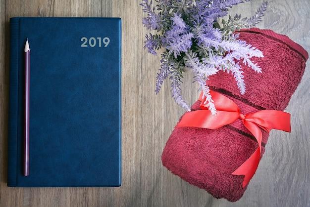 Взгляд сверху голубой тетради с карандашем, красным полотенцем и комнатным растением на деревянном столе.