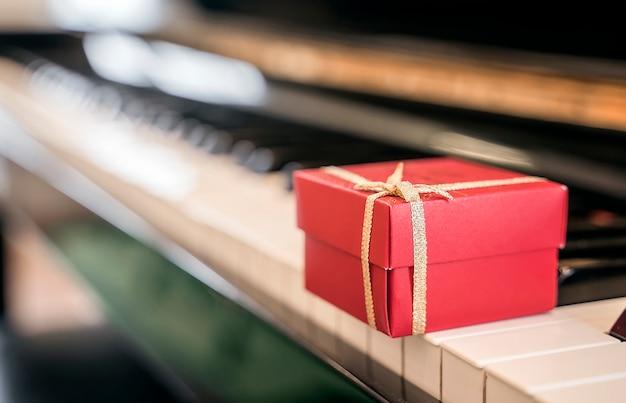 背景のピアノのキーボードの赤いギフトボックス。