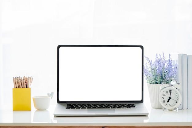 白いテーブルに空白の画面を持つモックアップノートパソコン。