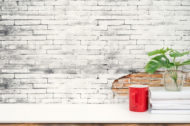 モックアップの赤カップ、書籍、製品の展示用コピースペースを持つ白いテーブルの上の観葉植物。