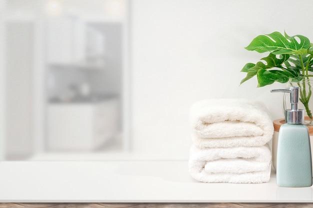 モックアップ白いタオルと製品展示用コピースペースの白いテーブルの上の観葉植物