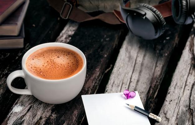 古い木製の背景にコーヒーの白いカップ。