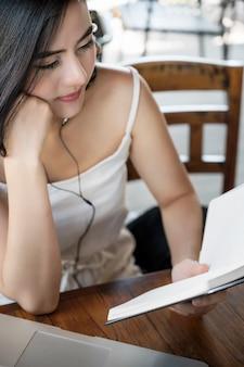 音楽を聴くと本を読むのコーヒーショップに座っている美しい女性。