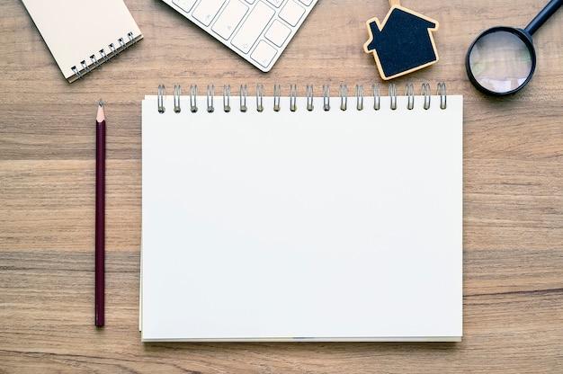 木製のテーブルの供給と空白のページノートブックの平面図です。