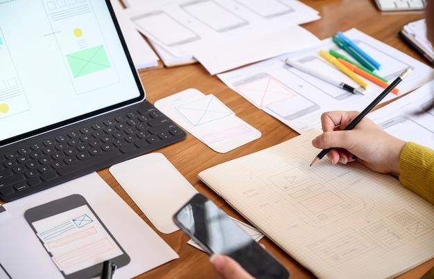 Рука женского дизайнера работая с ее новым проектом на офисе.