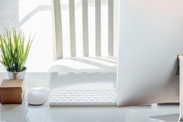 Мышь, пустая записка, карандаш, белая клавиатура, очки и комнатное растение на белом столе