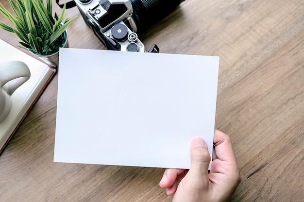 木製のテーブルにカメラを持つ白いカードを持っている人間の手のショット。上面図。