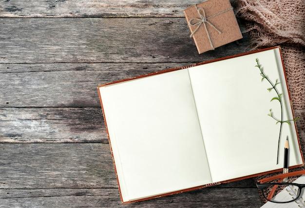 トップビューで木製のテーブルに開いているノートブックをモックアップします。
