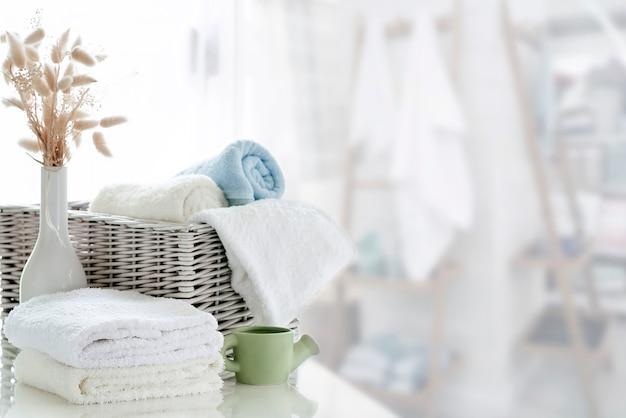Белые полотенца на белом столе с копией пространства на фоне светлой комнаты