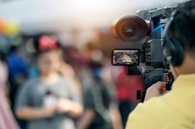 ビデオカメラ男の若い女性記者と屋外での作業。
