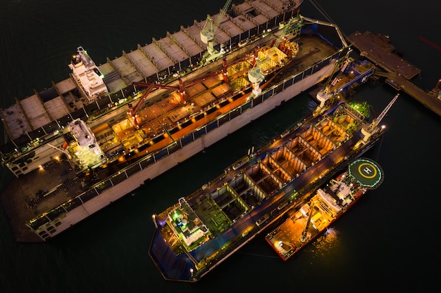 Промышленность верфи и ремонт больших кораблей в море с высоты птичьего полета ночью