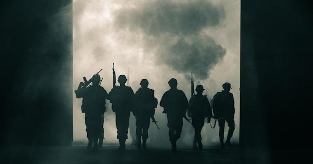 タイの兵士の特殊部隊は煙と手に銃を持って完全に均一な歩行行動