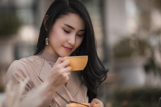 コーヒーを飲みながら座っているビジネス女性と公園でリラックスした幸せな笑顔