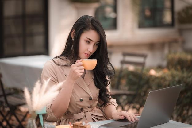 Деловые женщины сидят, пьют кофе и счастливые улыбающиеся отдыха в парке