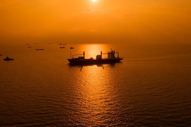 シルエット物流出荷貨物外海と夕日を背景に