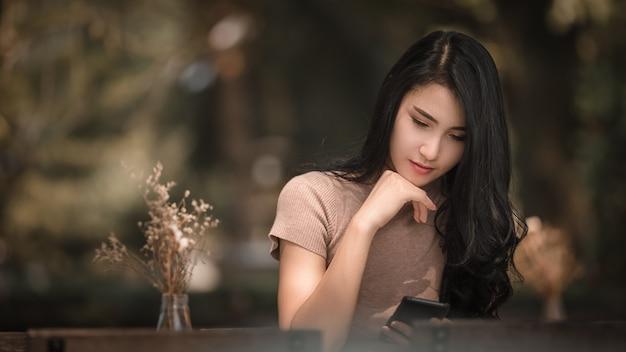 座っている美しいアジアの女性の女の子が公園で携帯電話でマッサージをチェックします。