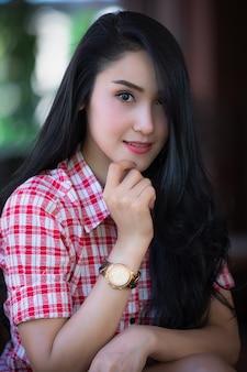 Портрет крупным планом жизни и улыбающийся тайский модельный профиль в красной рубашке скотта