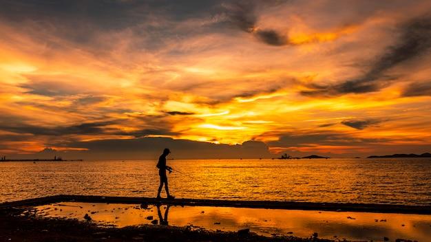 夕暮れの海の景色、タイの島の漁師シルエット前景と夕日とライトゴールド