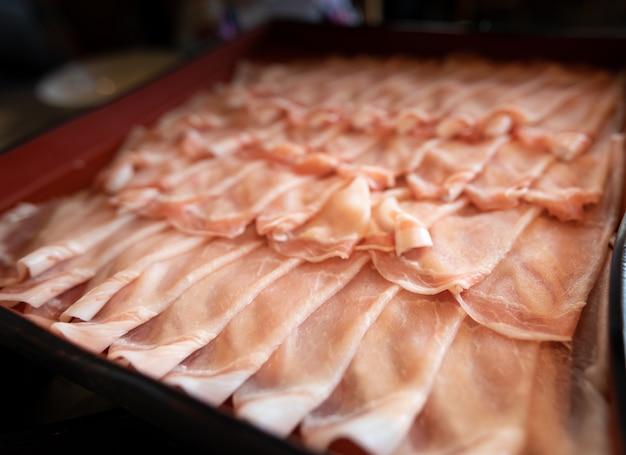 豚はレストラン日本のテーブルの上のコンテナー内の行にスライドします。