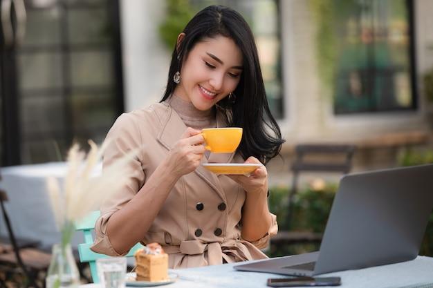 アジアビジネスの女性がコーヒーとケーキを飲む