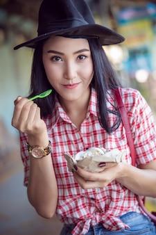 格子縞のシャツと黒い帽子でタイの女の子観光客はココナッツアイスクリームケーキを食べています。
