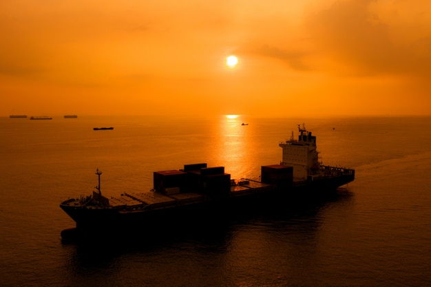 シルエットの出荷貨物コンテナーは夕方に海の国際輸出をインポートします