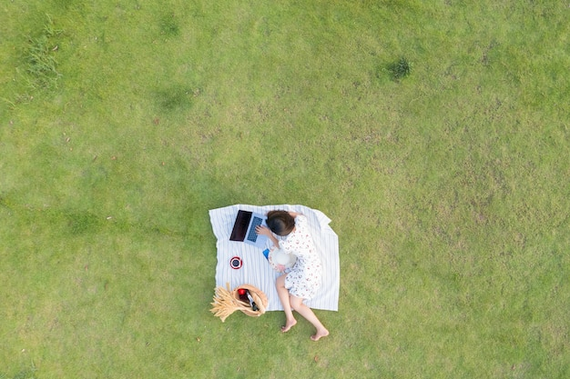 Азиатские женщины лгут о расслабляющем и работающем ноутбуке на зеленой траве