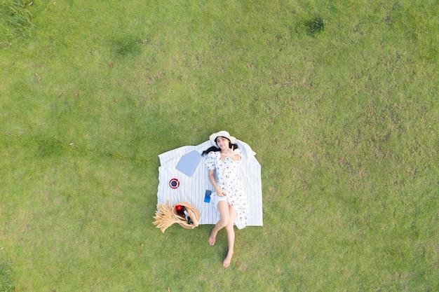 Азиатские женщины валяются и отдыхают на зеленой траве